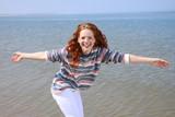 Hübsche rothaarige Frau steht lachend und mit ausgebreiteten Armen am Meer