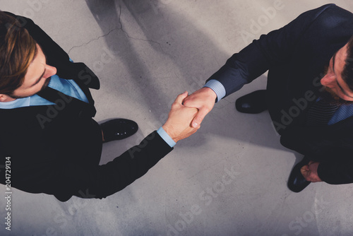 Handshaking business person in office. concept of teamwork and partnership