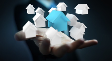 Businessman using 3D rendered small white and blue houses