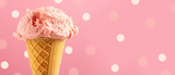 Ice cream. Strawberry or raspberry flavor icecream in waffle cone over pink polka dots background. Sweet dessert closeup