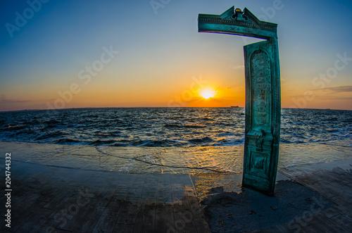 Aluminium Zee zonsondergang Sun rising behind the old green door on the beach in Odessa. Fisheye wide view