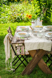 Table with homemade chicken soup in summer garden