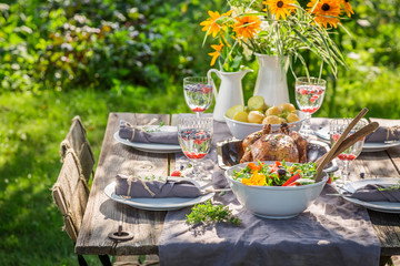 Dinner with salad and chicken served in summer garden