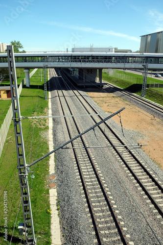 Plexiglas Spoorlijn Urban industrial landscape railroad tracks, platform and elevated pedestrian crossing on sunny summer day top view