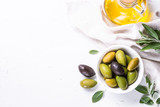 Olives and olive oil on white.