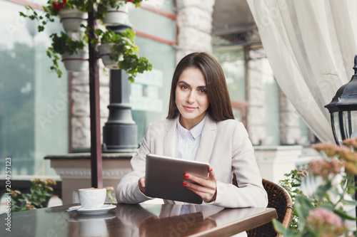 Poster Young businesswoman outdoors working with laptop