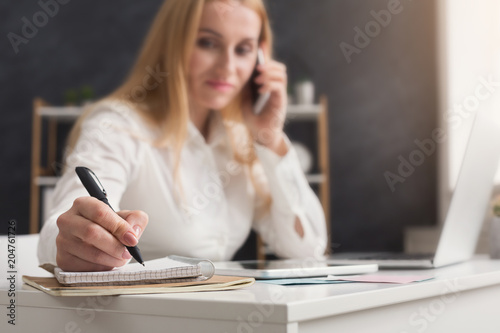 Serious business woman at work talking on phone