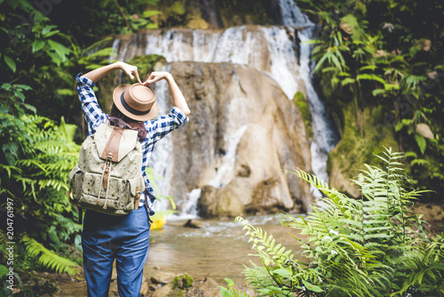 Travel and freedom. Young woman in hat with rucksack enjoying tropical waterfall view.