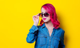 Young pink hair girl in sunglasses and blue shirt. Portrait on yellow background