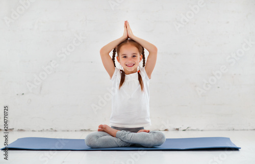 child girl doing yoga and gymnastics in gym