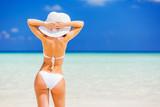 Back of young woman in bikini standing on the beach - 204773342