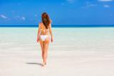 Young woman in bikini walking on the beach