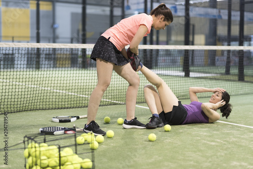 woman is injured during padel match and the other helps