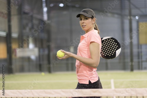 Plexiglas Tennis One woman with racquet and ball behind the net in paddle tennis court ready for training