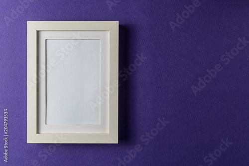 Styl minimalizmu. Biała pusta ramka na zdjęcia; abstrakcyjne kolorowe tło papieru; płaskie lay