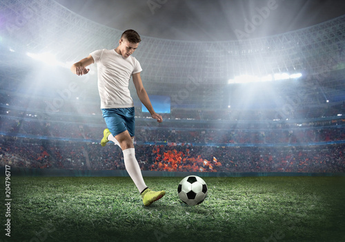 Soccer player on a football field in dynamic action at summer day - 204796717