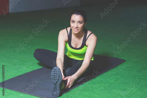 Sporty young woman makes sport exercises in the gym