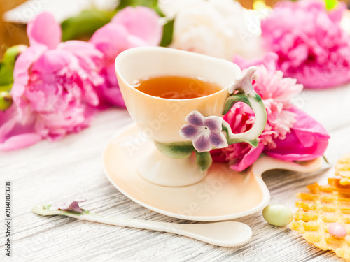 Fototapeta Cup of green tea and spring peonies blossom on a old wooden background with waffles and caramels. Rustic.