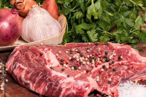 Plexiglas Steakhouse steak of beef on a wooden board with spices pepper parsley salt onions shallots garlic