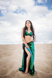 Dancer bellydance in a black and green shiny suit in the desert against the background of sand. Beautiful nature. Belly dance. A girl with an exotic appearance. Oriental beauty.