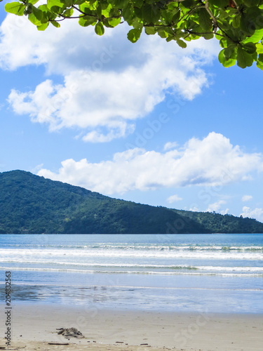 Fotobehang Tropical strand View of quiet beach in sunny day with blue sea and island in the background.