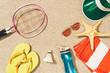 top view of badminton equipment, sunglasses, flip flops, cap and towel on sand - 204835960
