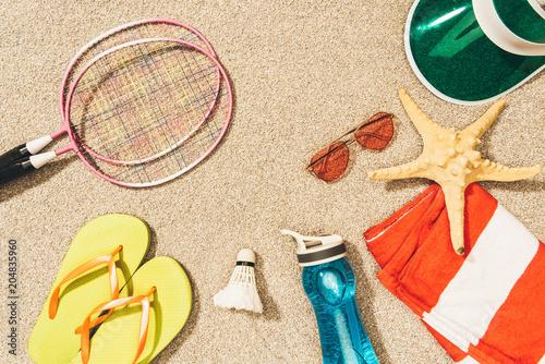 Sticker top view of badminton equipment, sunglasses, flip flops, cap and towel on sand