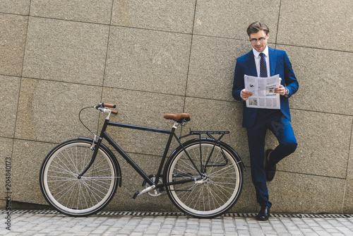 Fototapeta handsome young businessman in stylish suit with bicycle reading newspaper leaning on wall