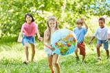 Glückliches Mädchen trägt Weltkugel