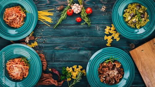 Poster A set of cooked pastes in plates. On a wooden background. Italian cuisine. Top view. Copy space.