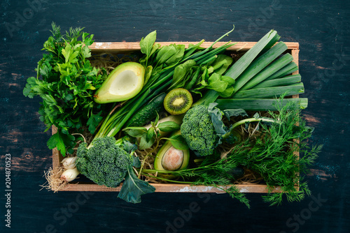 Foto Murales Fresh green vegetables and fruits in a wooden basket. Healthy food. Top view. Copy space.