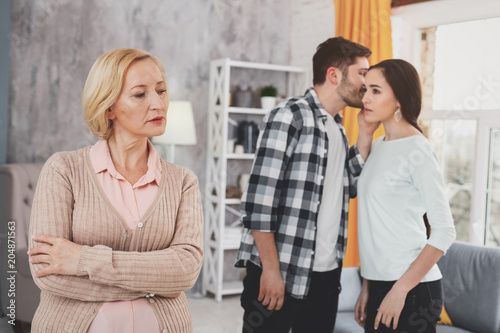 Private talk. Curious aged woman standing in the living room while trying to overhear the conversation between her daughter and her boyfriend