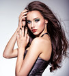 Beautiul woman with long brown hairs and green make-up and   nails