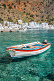 Fishing boat and the scenic village of Loutro in Crete, Greece - 204880165