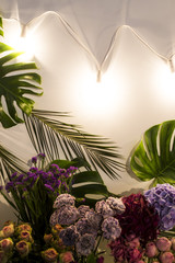 Tropical leaves and flowers with lanterns on white. Background