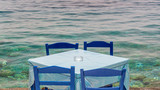 Restaurant tables by the sea in a village of Crete, Greece - 204883720