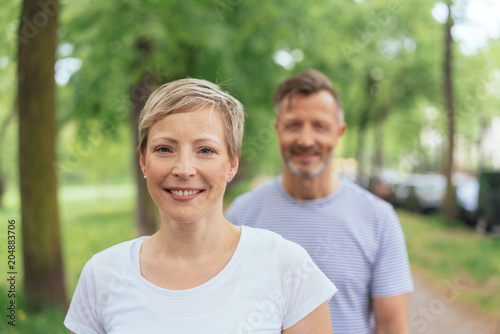 Fototapeta Cheerful mature woman with man in background