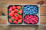 Mix of organic berries. Baskets of fresh raspberries, blueberries,strawberries on wooden table, top view - 204885146