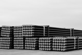 Rows of Steel Pipes storage and stacking outside warehouse for industrial construction in Black and white.