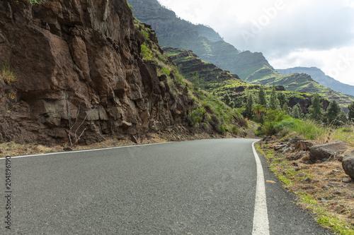 Poster Asphaltierte Straße mit Kurve im Gebirge
