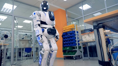 Human-like robot is rotating its head and looking into the camera