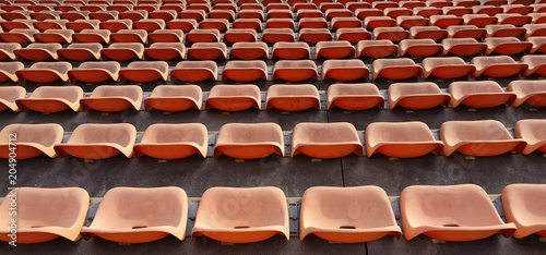 rows of empty plastic seat chairs on a stadium