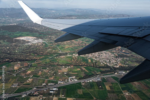 View through the window of the wing of an airplane flying above the countryside
