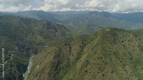 Aluminium Bergrivier Aerial view of mountain river in the cordillera, road on the slopes, mountains covered forest, trees. Cordillera region. Luzon, Philippines. Mountain landscape sky with clouds.