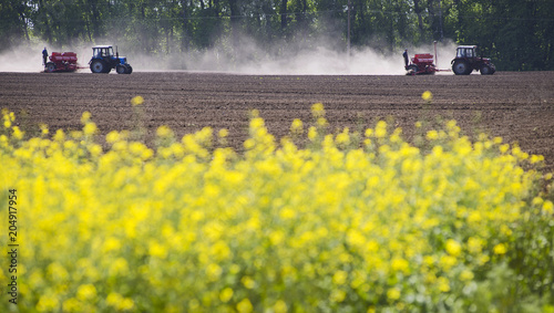 Aluminium Trekker Two tractors working in the field have a dust on them. Yellow rapeseed field background.