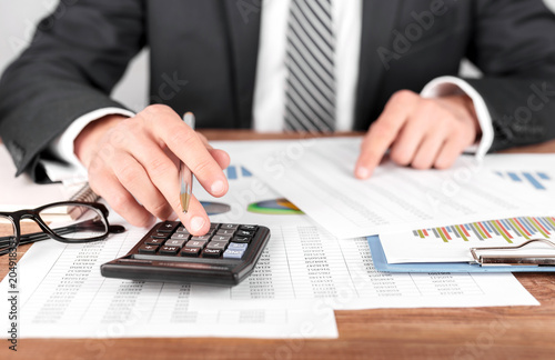 Businessman working with using a calculator to calculate the numbers. Finance accounting concept © Michail Petrov