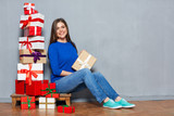 Smiling happy woman sitting on floor with pile of presents and h