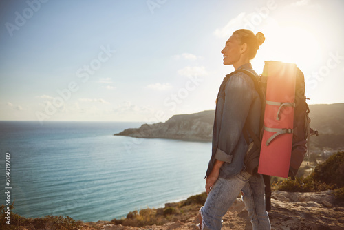 Profile of cheerful girl with big knapsack behind her back enjoying sea view while standing on hill. Copy space in left side