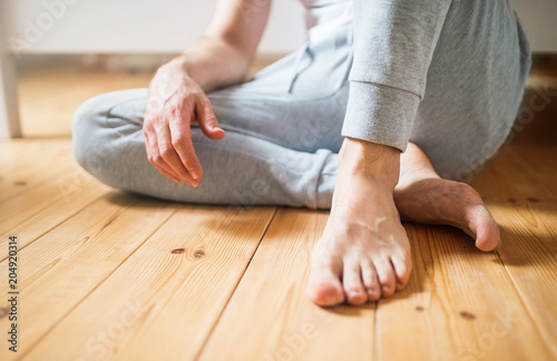 Unrecognizable man sitting on the floor in bedroom at home.