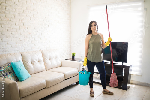 Stressed woman standing holding broom and bucket in living room